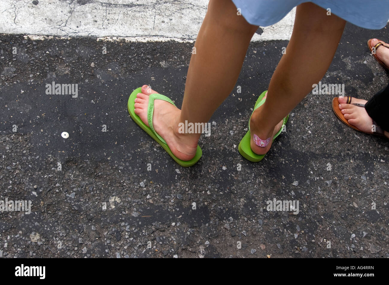 Woman wears flip flops with band aids on her heels Stock Photo