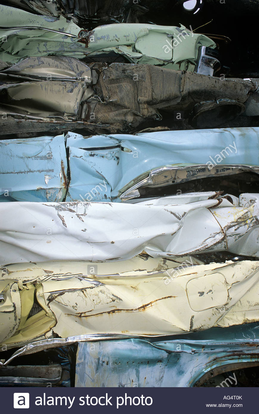 Crushed cars at wrecking yard waiting to be sold for scrap metal - Stock Image