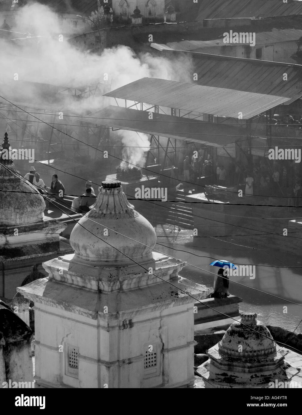 View over Pashpatinath, Kathmandu with cremations and blue umbrella - Stock Image