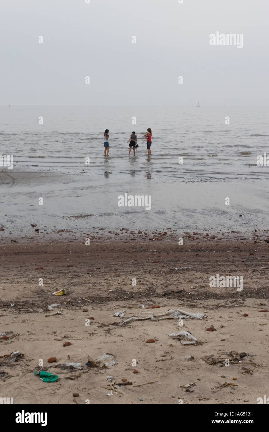 Three Figures Paddling in a Polluted Sea - Stock Image