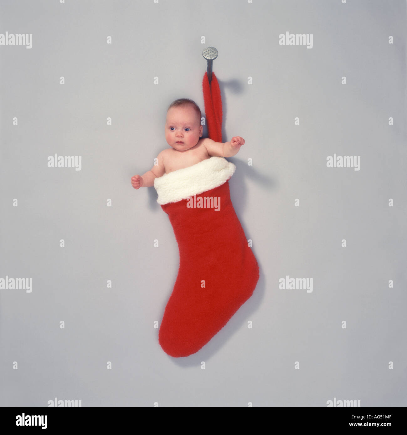 Baby in a hanging Christmas sock - Stock Image