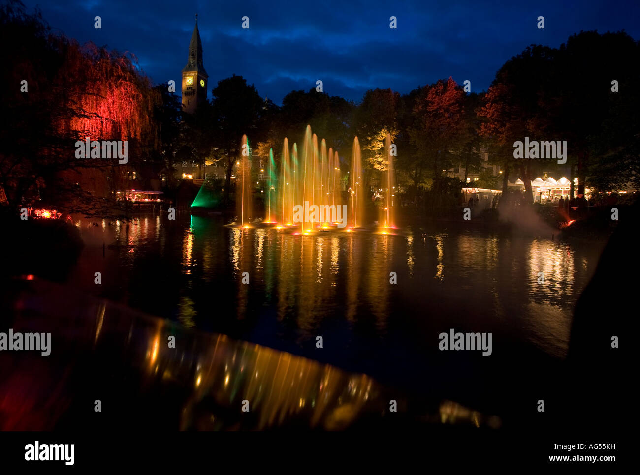 Laser and Fountain Show Yellow Fountains of water glow with the light reflected from lasers and coloured lights - Stock Image