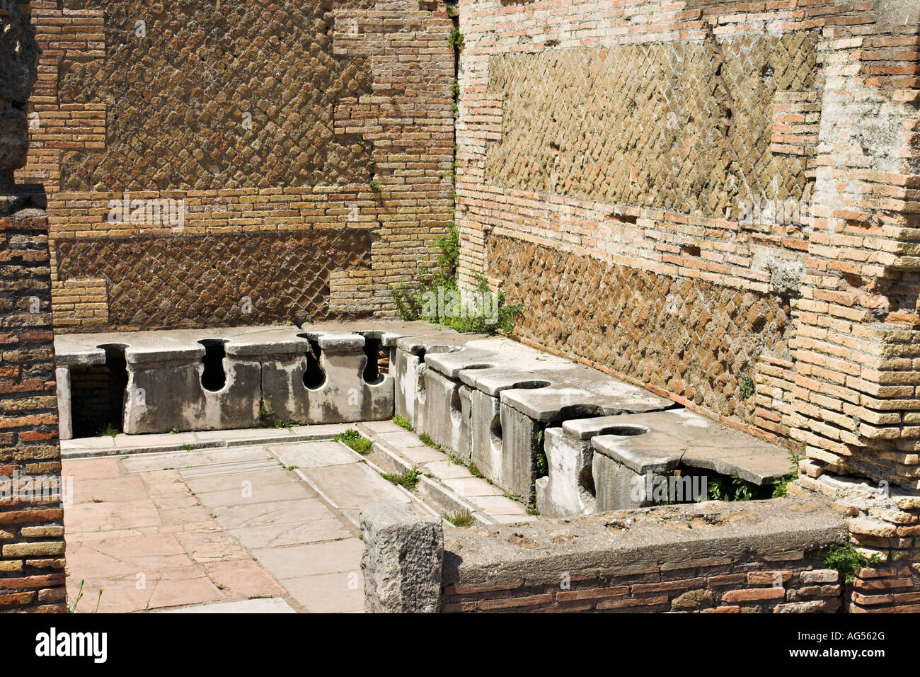 Ancient Toilet WC A room lined with stone toilets surrounded by old brick and underlaid with an elaborate plumbing - Stock Image