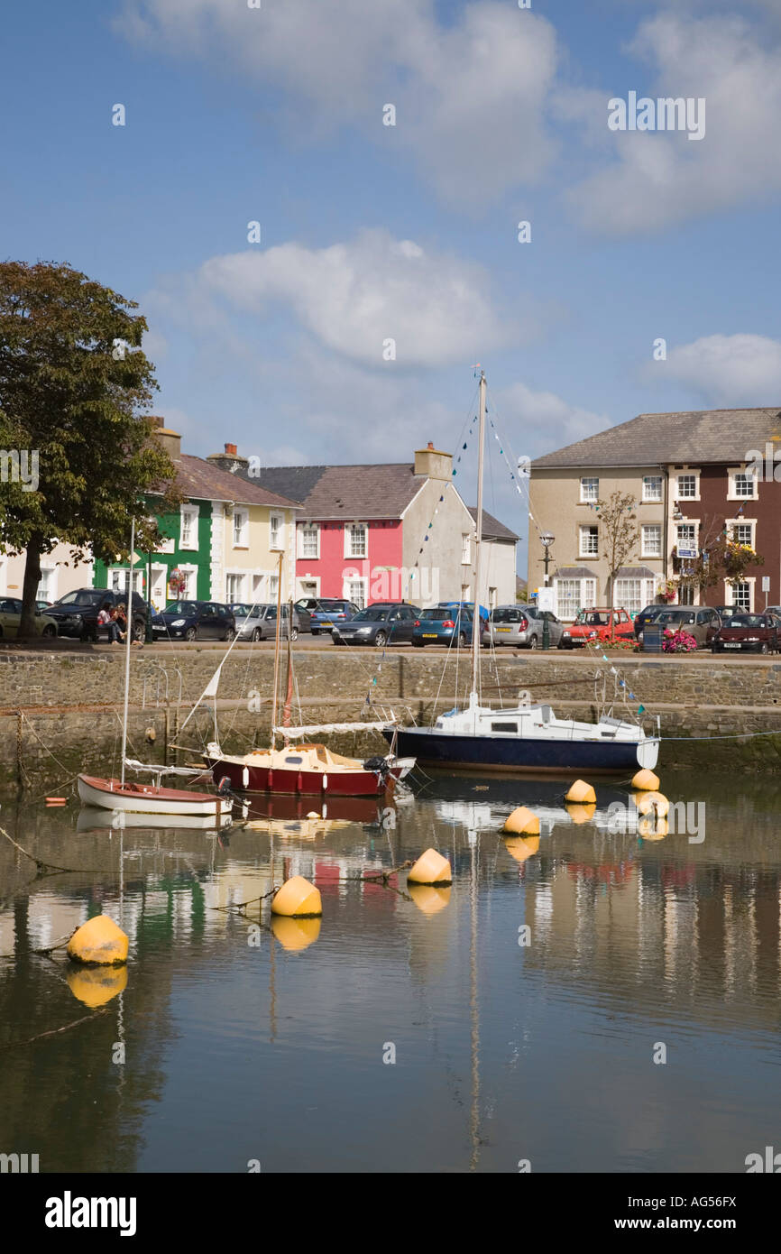 Attractive colourful quayside Georgian houses reflected in calm water of harbour with moored boats Aberaeron Ceredigion - Stock Image