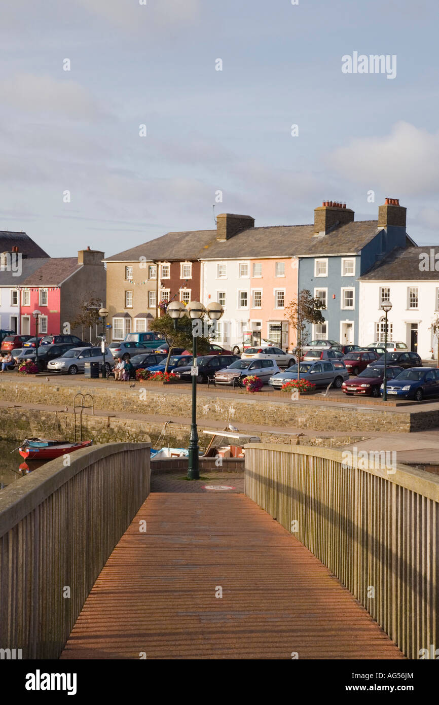 View along wooden footbridge across Afon Aeron River to harbour with colourful Georgian houses Aberaeron Ceredigion - Stock Image