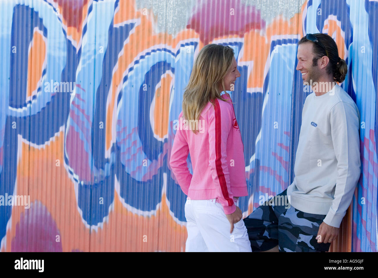 Couple talking and flirting leaning on wall Stock Photo