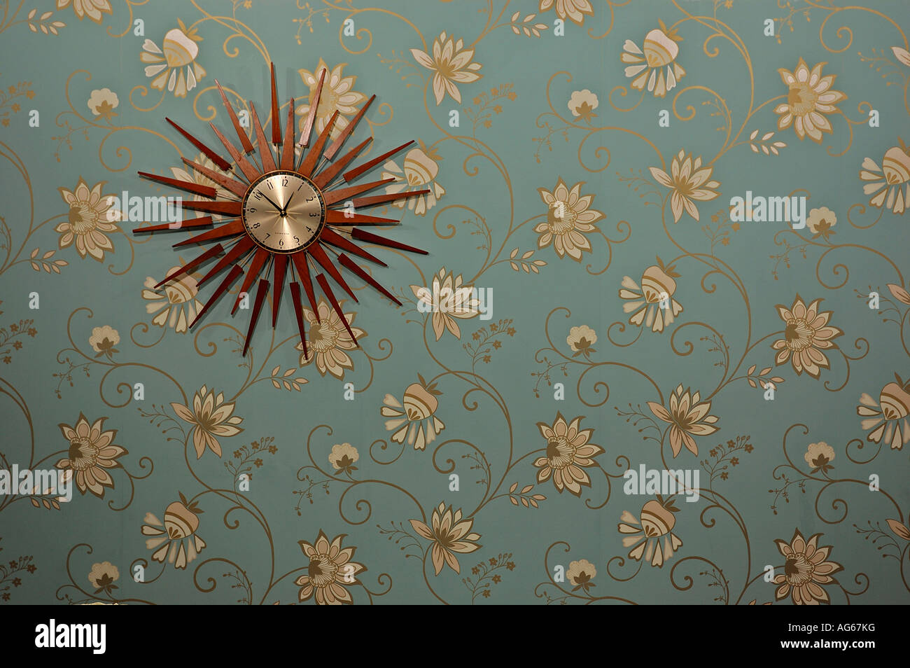 Close-up of sunburst clock on modern blue wallpaper with gold and cream stylised flower pattern - Stock Image