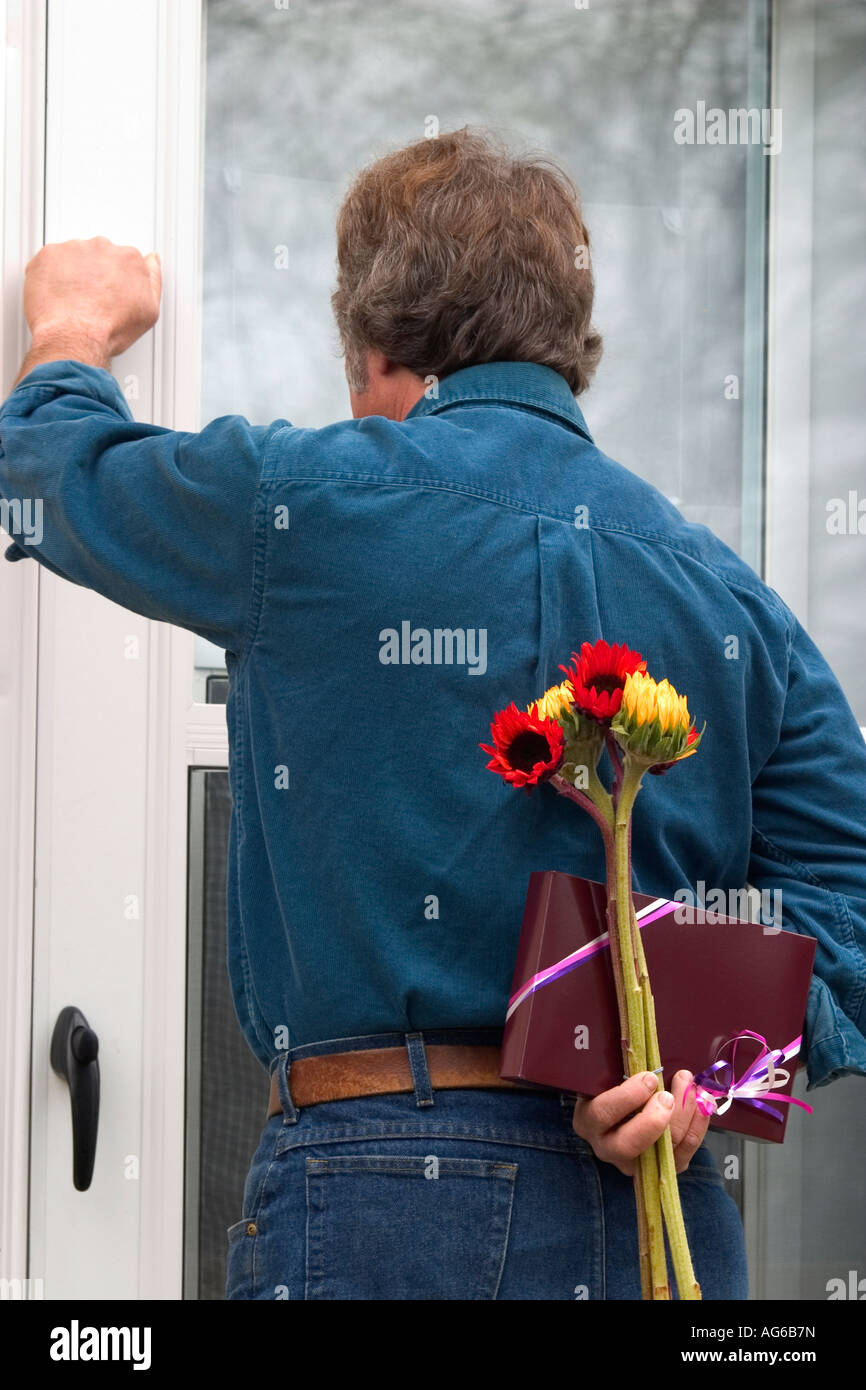 Caucasian man knocking on the door with a box of candy and flower caucasian man knocking on the door with a box of candy and flower bouquet behind his back izmirmasajfo