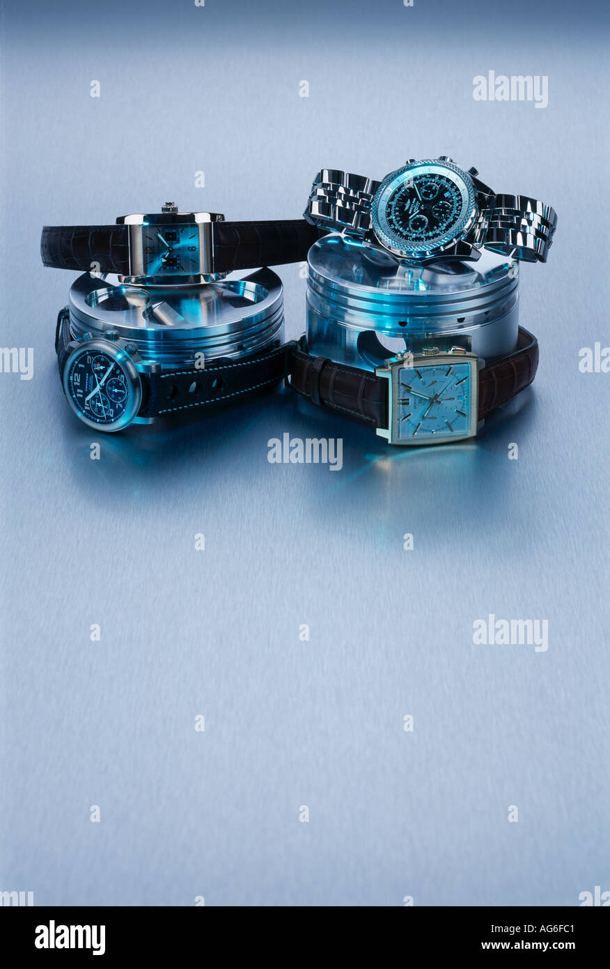 Watches on car piston heads blue lit aluminium backround Stock Photo