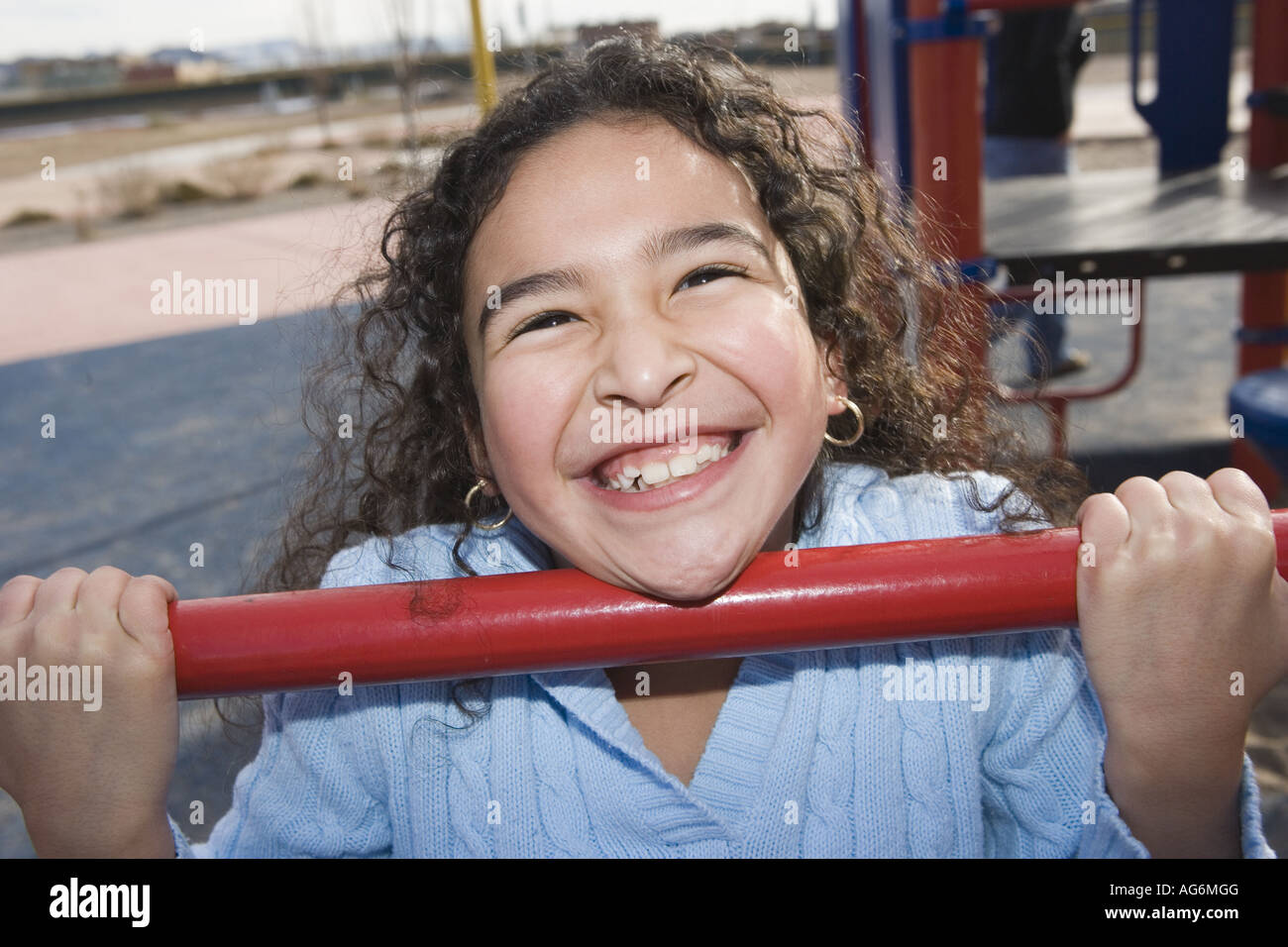 ten year old girl hanging on to bar on school playground, big bright toothy grin - Stock Image