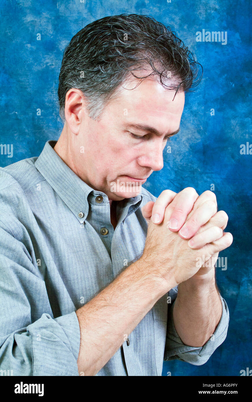 A man in a posture of prayer with head bowed and hands together - Stock Image
