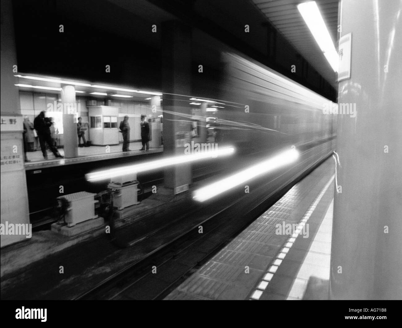 Japanese ghost train. High speed train rushing through station causing bluured ghost like image - Stock Image