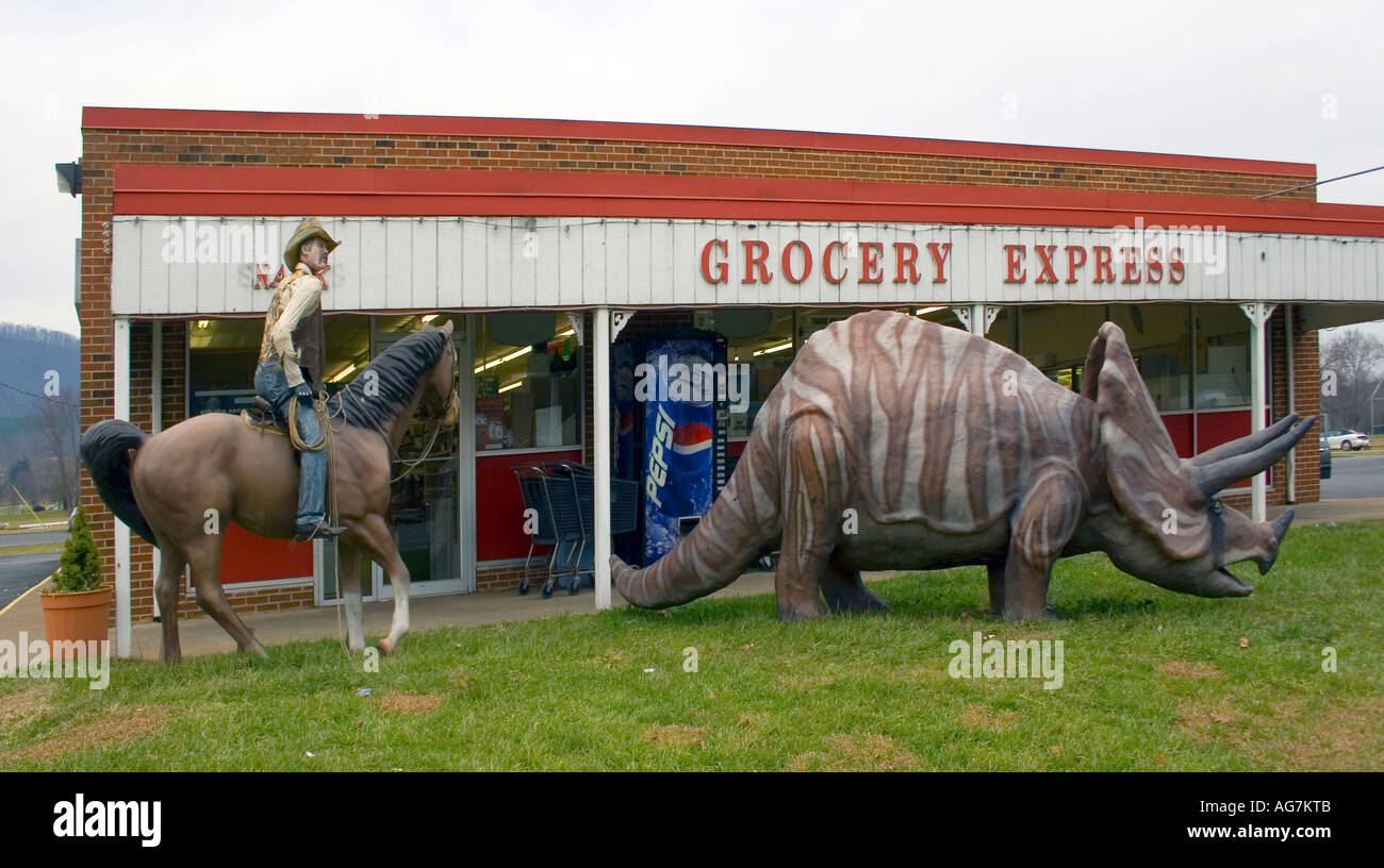 Cowboy and Dinosaur in front of a grocery store at the Town Time Forgot in Glasgow Virginia - Stock Image