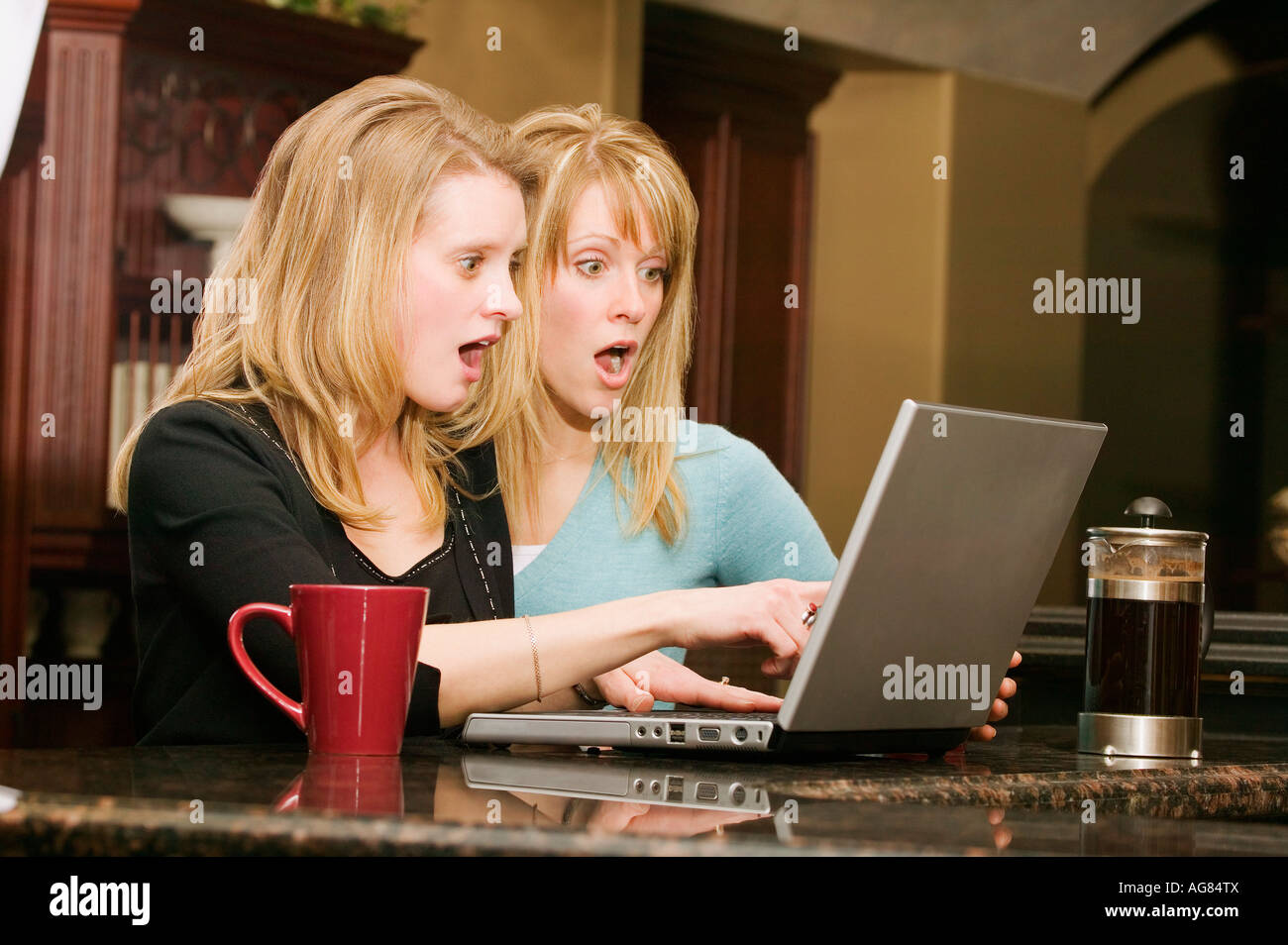 Woman with surprised expressions looking at a laptop - Stock Image