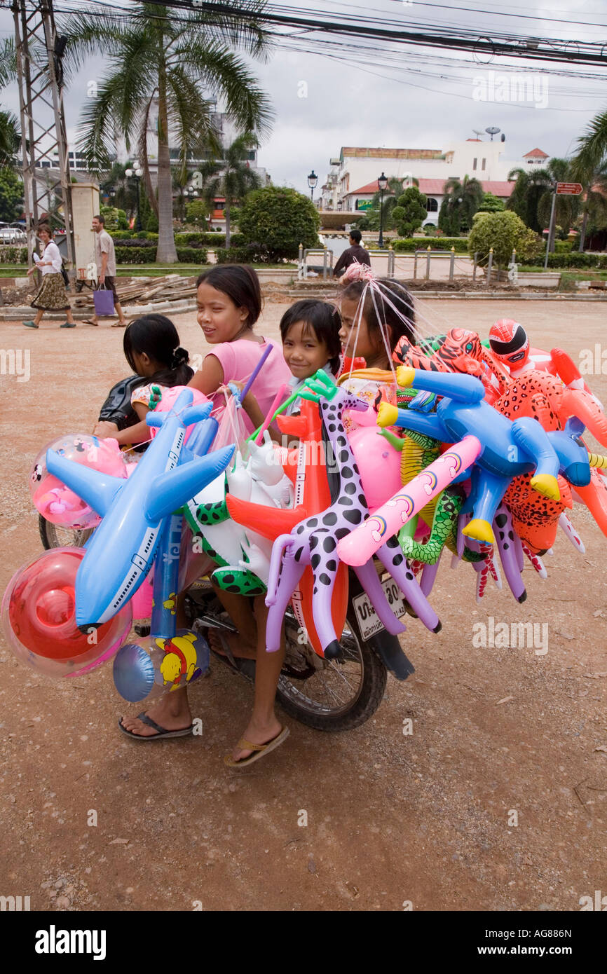 Laos family on a motorcycle in Vientiane with their Inflatable toys for sale Stock Photo
