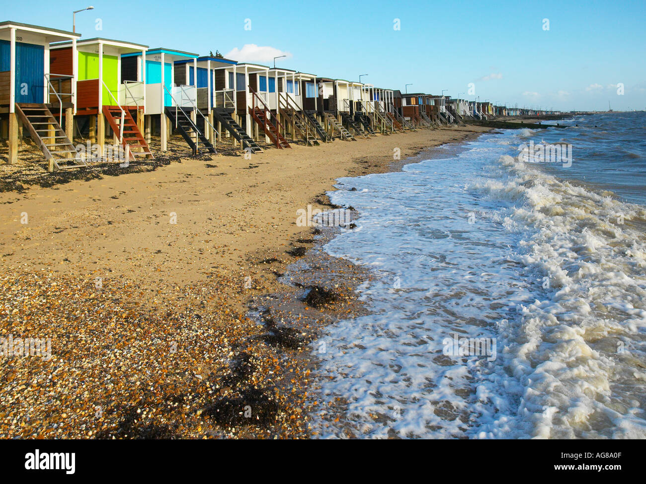 colourful beach huts along the seashore with waves gentley foaming and blue skies on a warm day at southend on sea Stock Photo