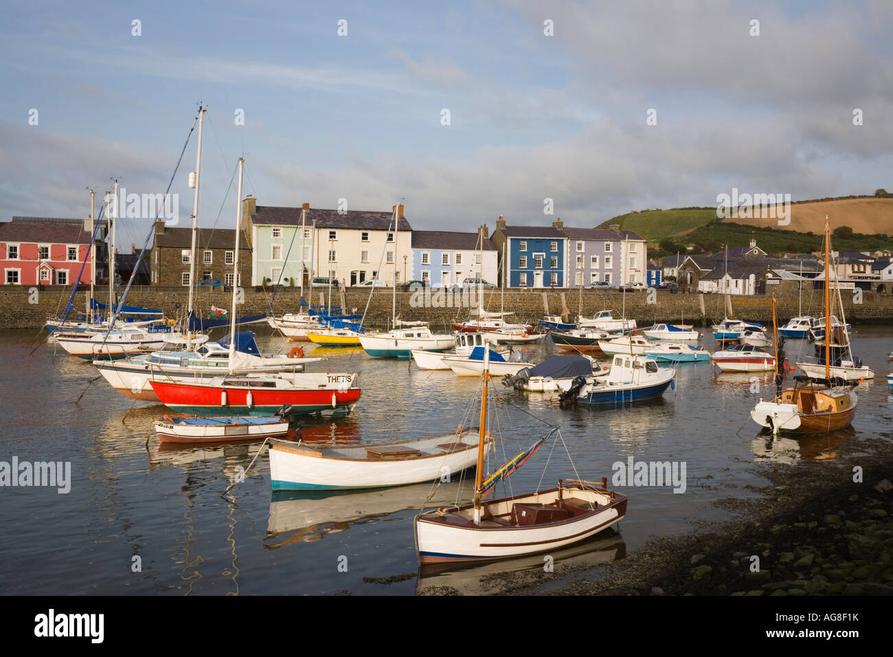 View across harbour with boats moored and colourful Georgian quayside houses in seaside town Aberaeron Ceredigion - Stock Image