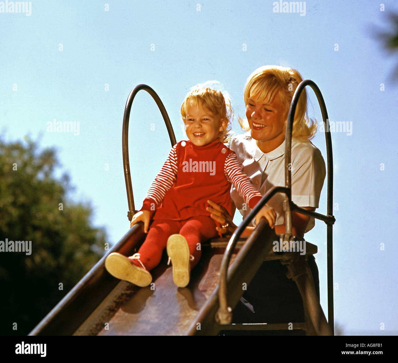 mother and young daughter playing on slide in park - Stock Image