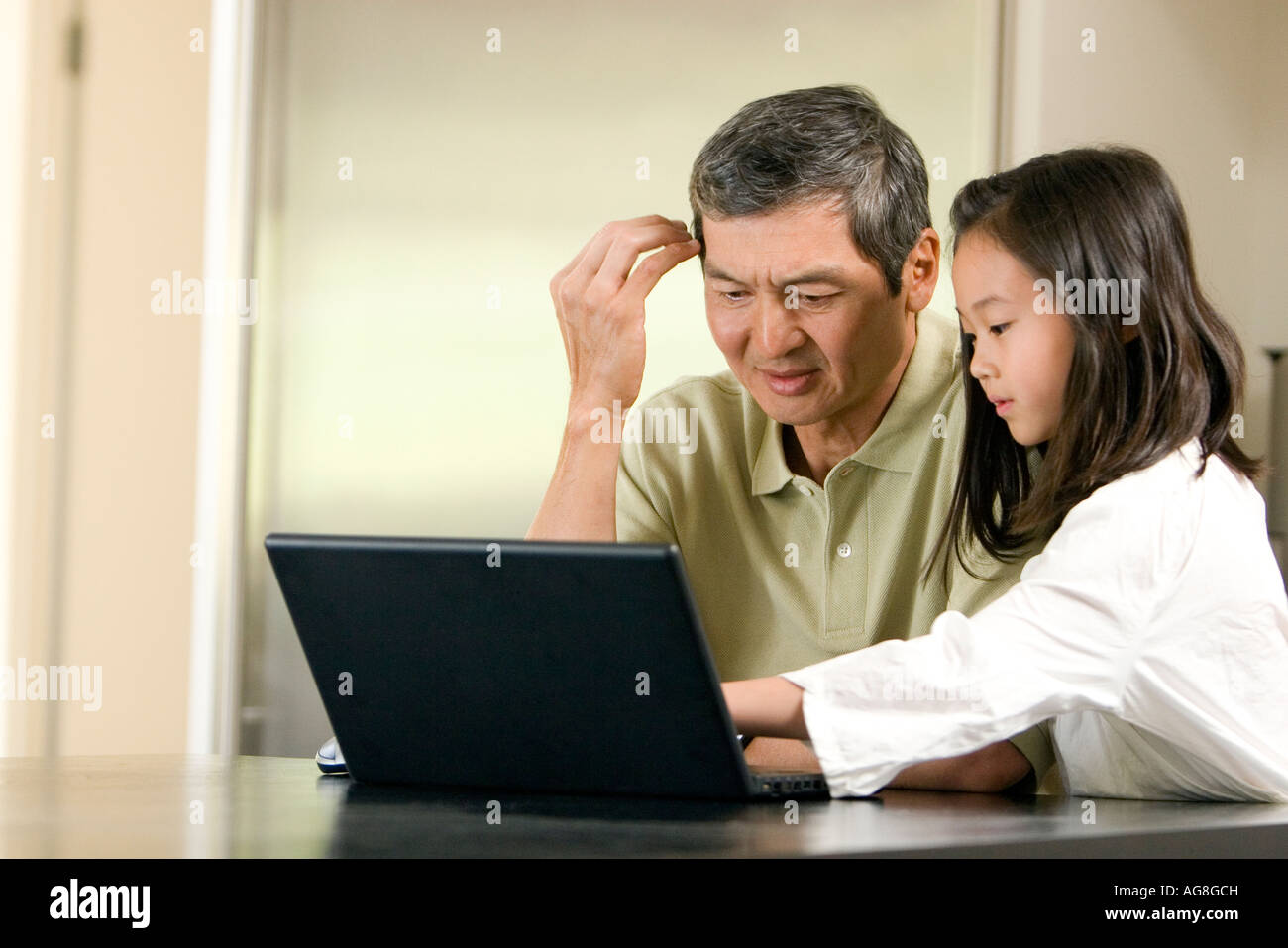 Grandfather and Granddaughter on Laptop - Stock Image