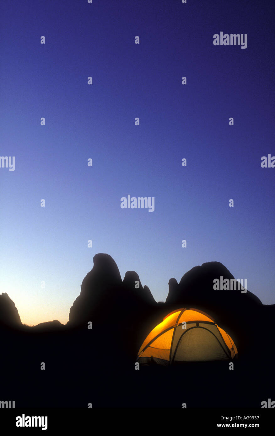 Glowing camping tent in the early evening with mountain peaks in background Property released image - Stock Image