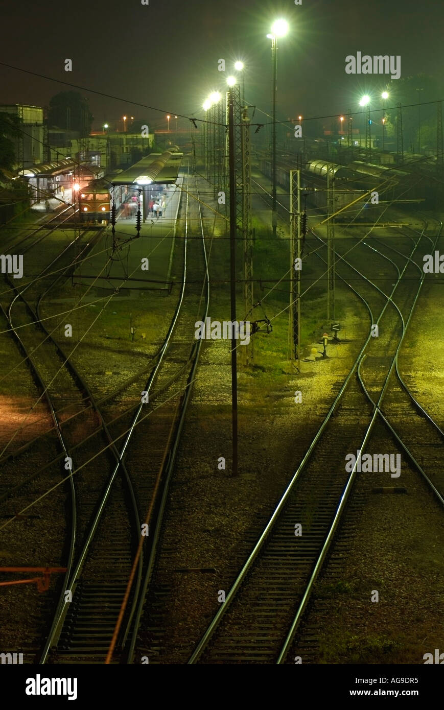 Railway Tracks Leading Into a Train Station and Freight Yard at Night - Stock Image