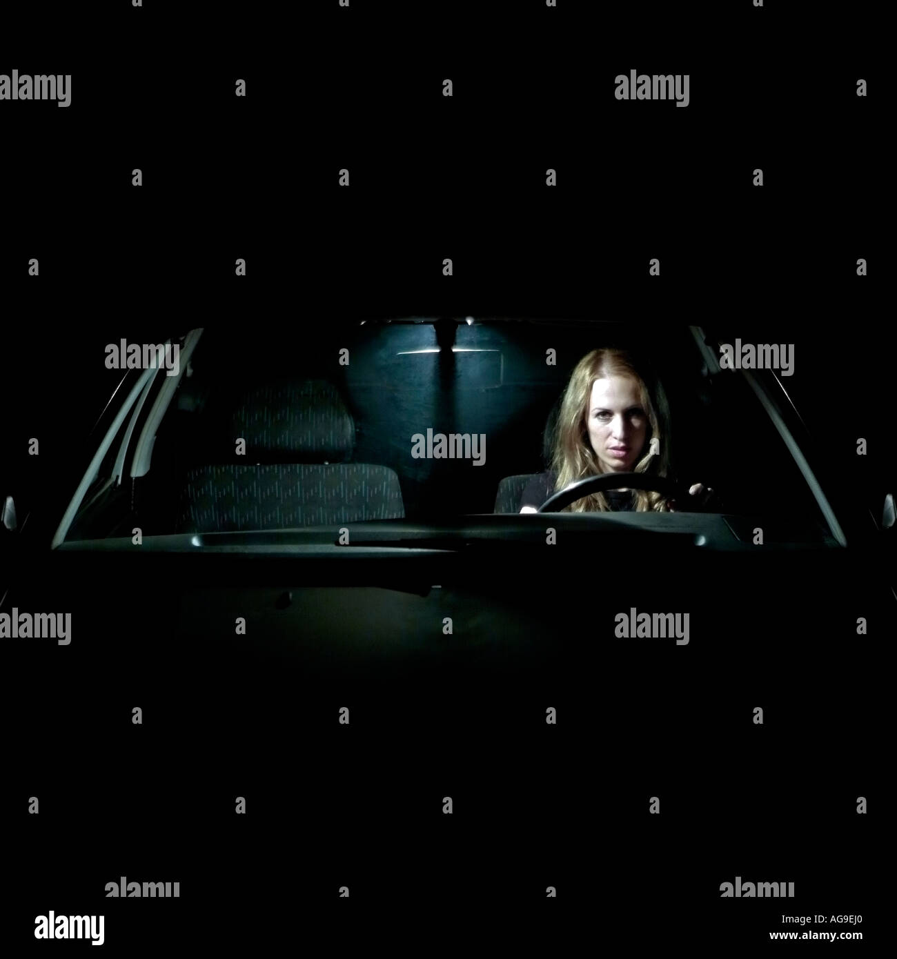 Caucasian Female Sat Alone In a Car at Night Illuminated by the Interior Light - Stock Image