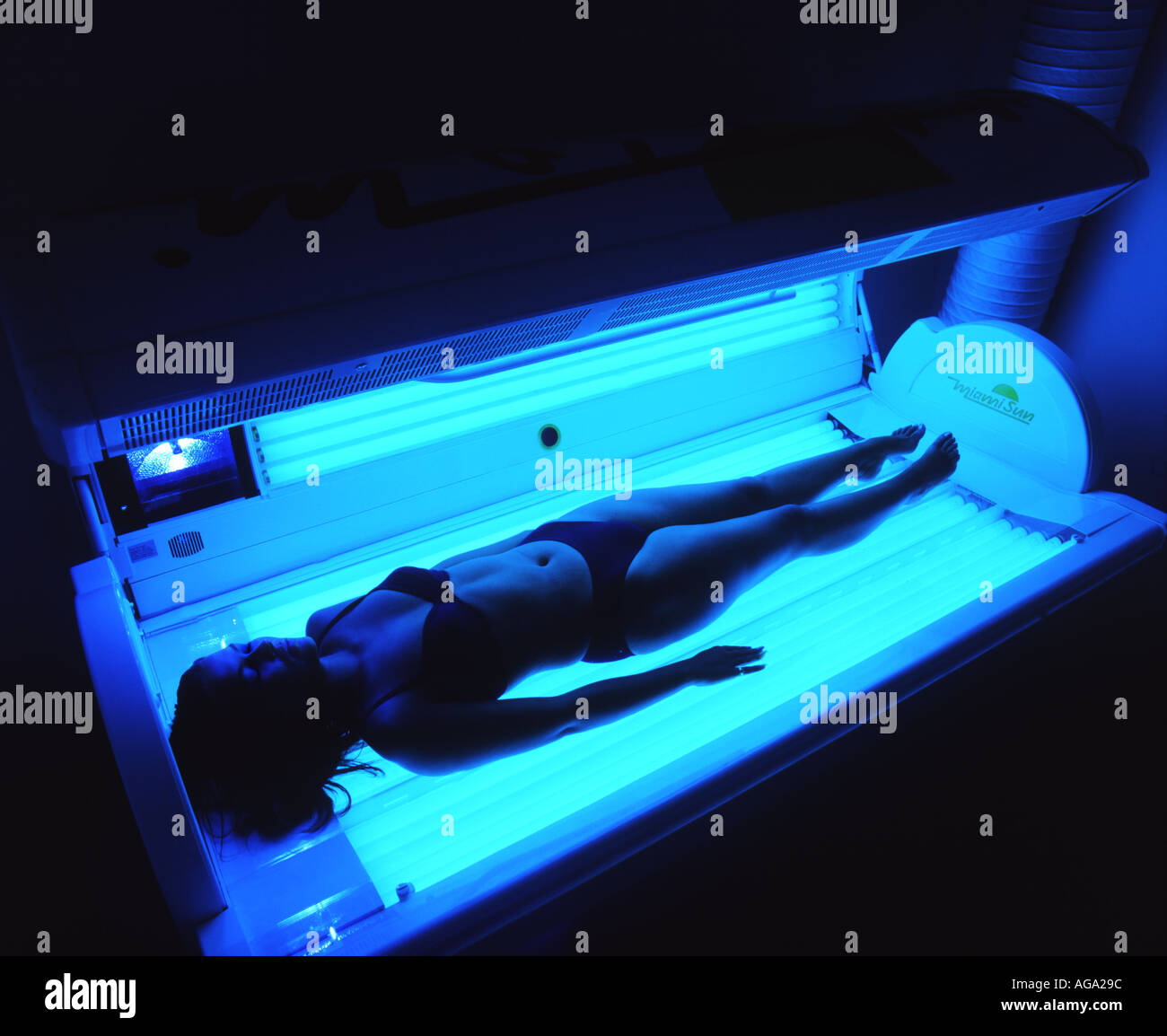 Girl lying on a sun bed - Stock Image