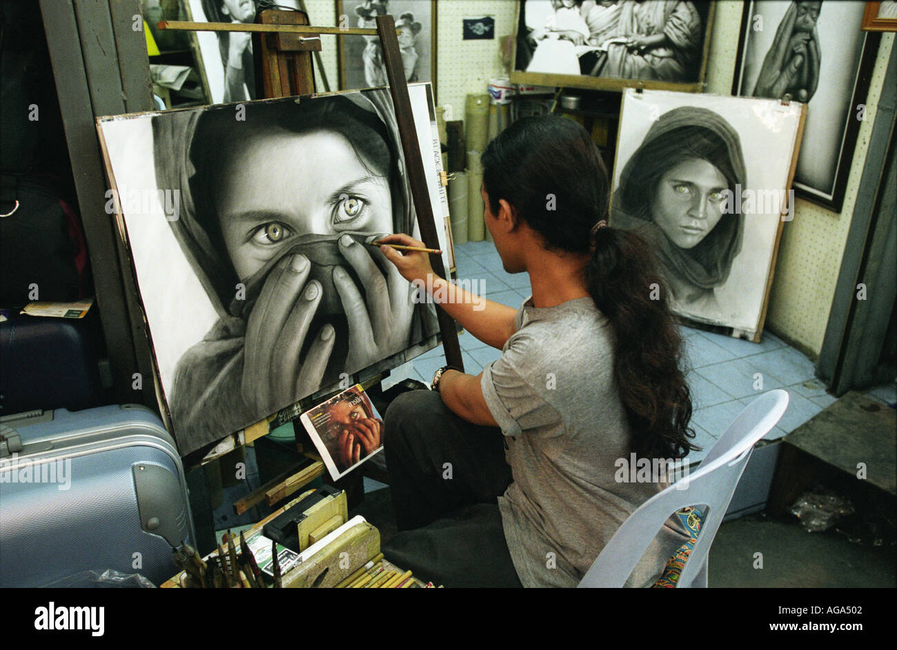 Drawing a picture taken from National Geographic Magazine at the Night Market in Chiang Mai Thailand - Stock Image
