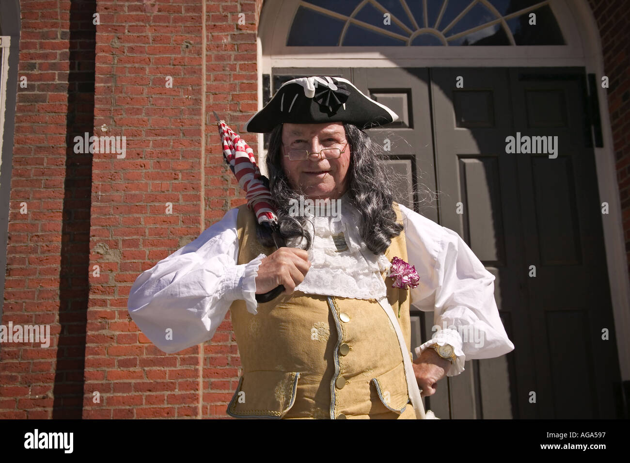 A colonial costumed gentleman dressed to look like Benjamin Franklin poses for photographs at Faneuil Hall in Boston MA - Stock Image