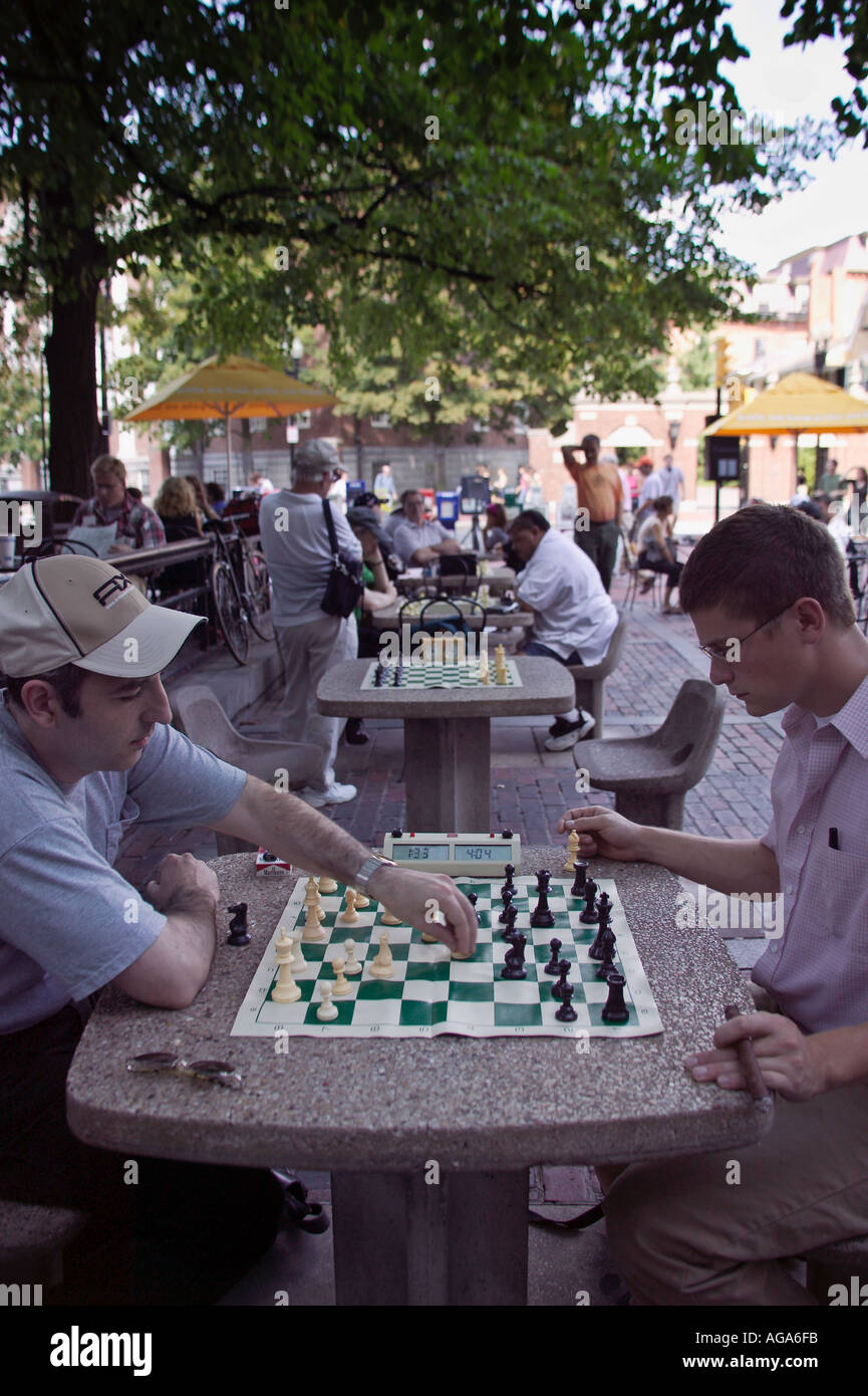 People playing chess in Harvard Square on stone tables in plaza across from Harvard University Cambridge MA - Stock Image