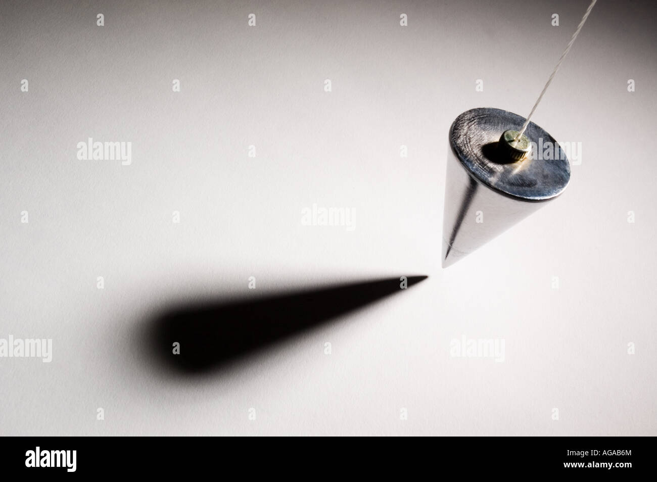 Plumb bob suspended above white surface Stock Photo