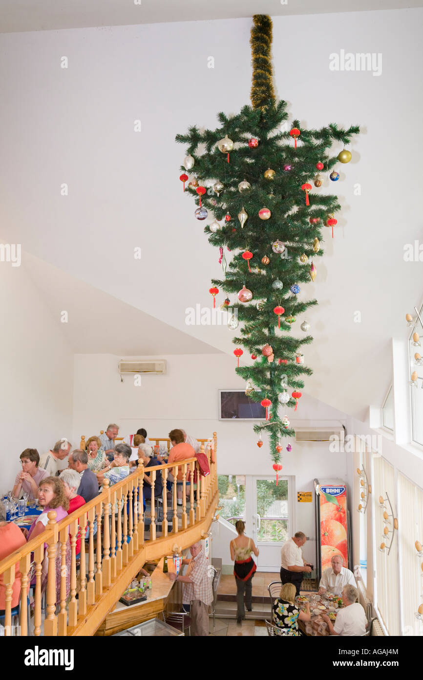 A decorated fir tree attached to the ceiling upside down in the hotel 'Liman' - Stock Image