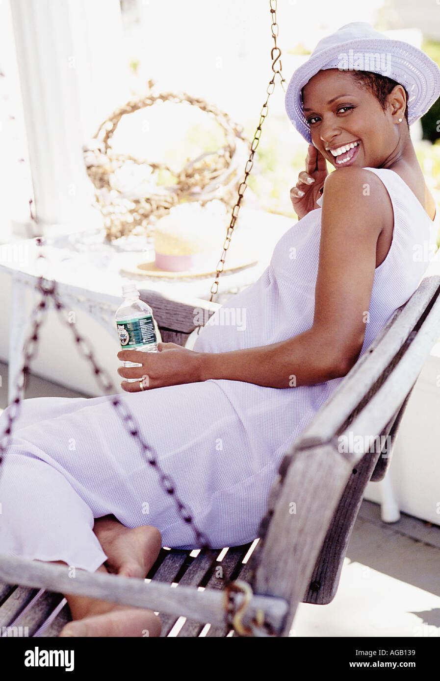 Pregnant Afro American woman on swing with Evian water - Stock Image