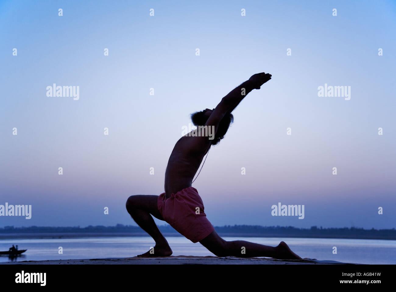 World famous yogi teacher Dr Rakesh Yogi in virbhadrasana yoga posture Ganges River India - Stock Image