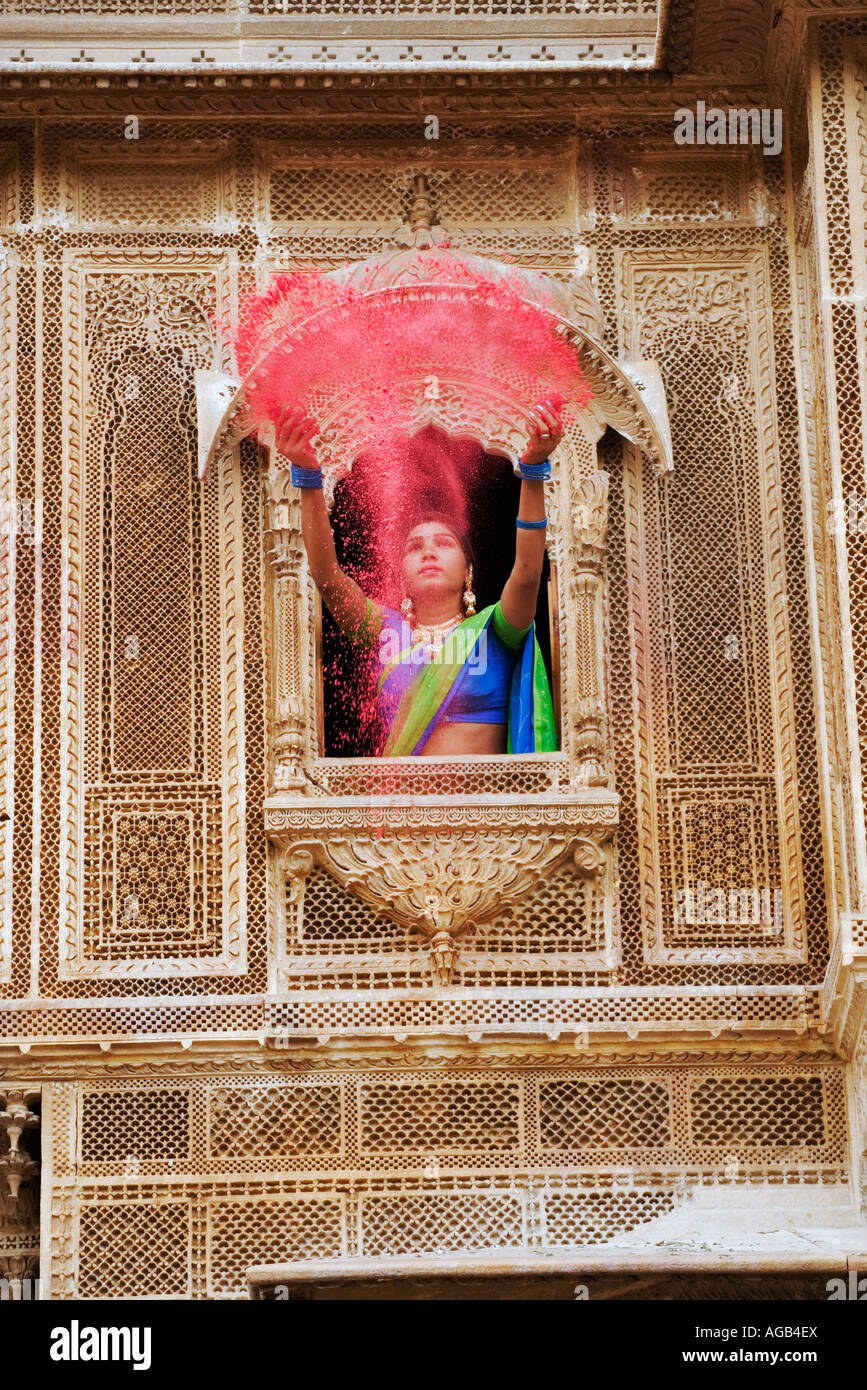 Woman throwing brightly coloured holi powder through a window of a haveli Stock Photo