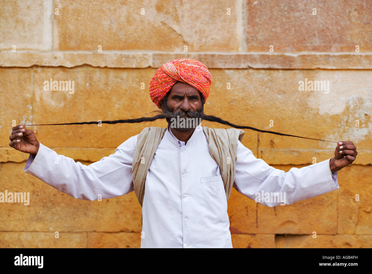 Portrait of an Indian man stretching out his 4 5 ft moustache - Stock Image