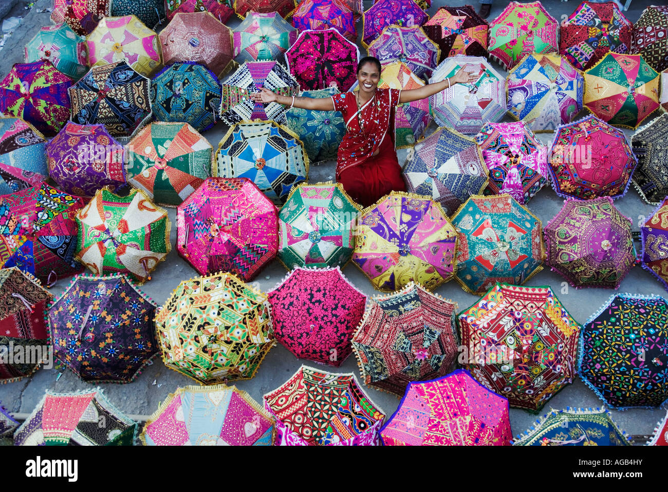 Woman in sari admiring colourful umbrellas outside a shop Jaipur India Model Released Property Released - Stock Image