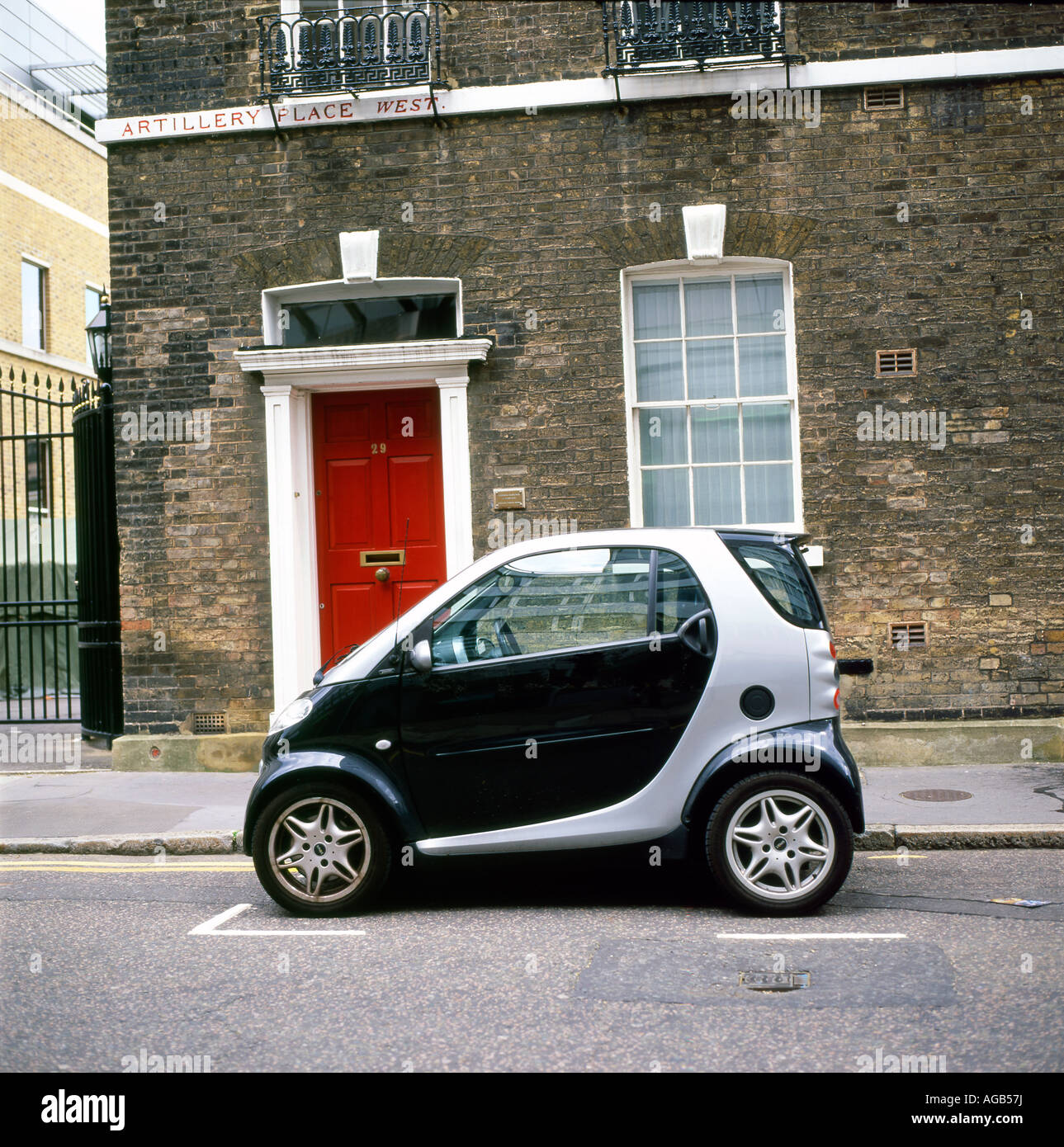 A Smart Car parked outside a stone terraced house with a red door on Artillery Row West, Bunhill Row, Finsbury, Stock Photo