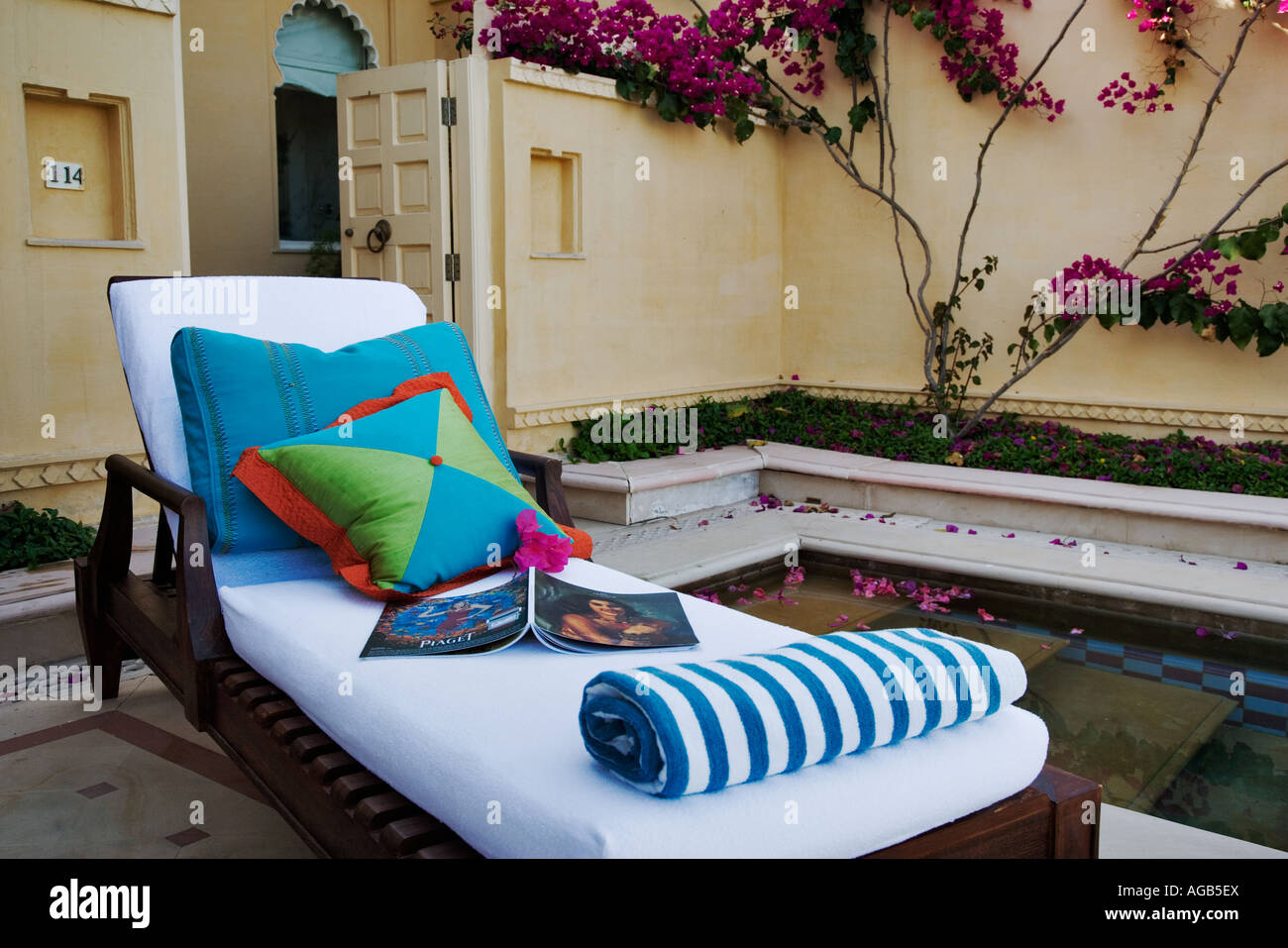Deckchair next to the crystal clear pool of the exclusive Udaivilâs Oberoi Hotel in Udaipur - Stock Image
