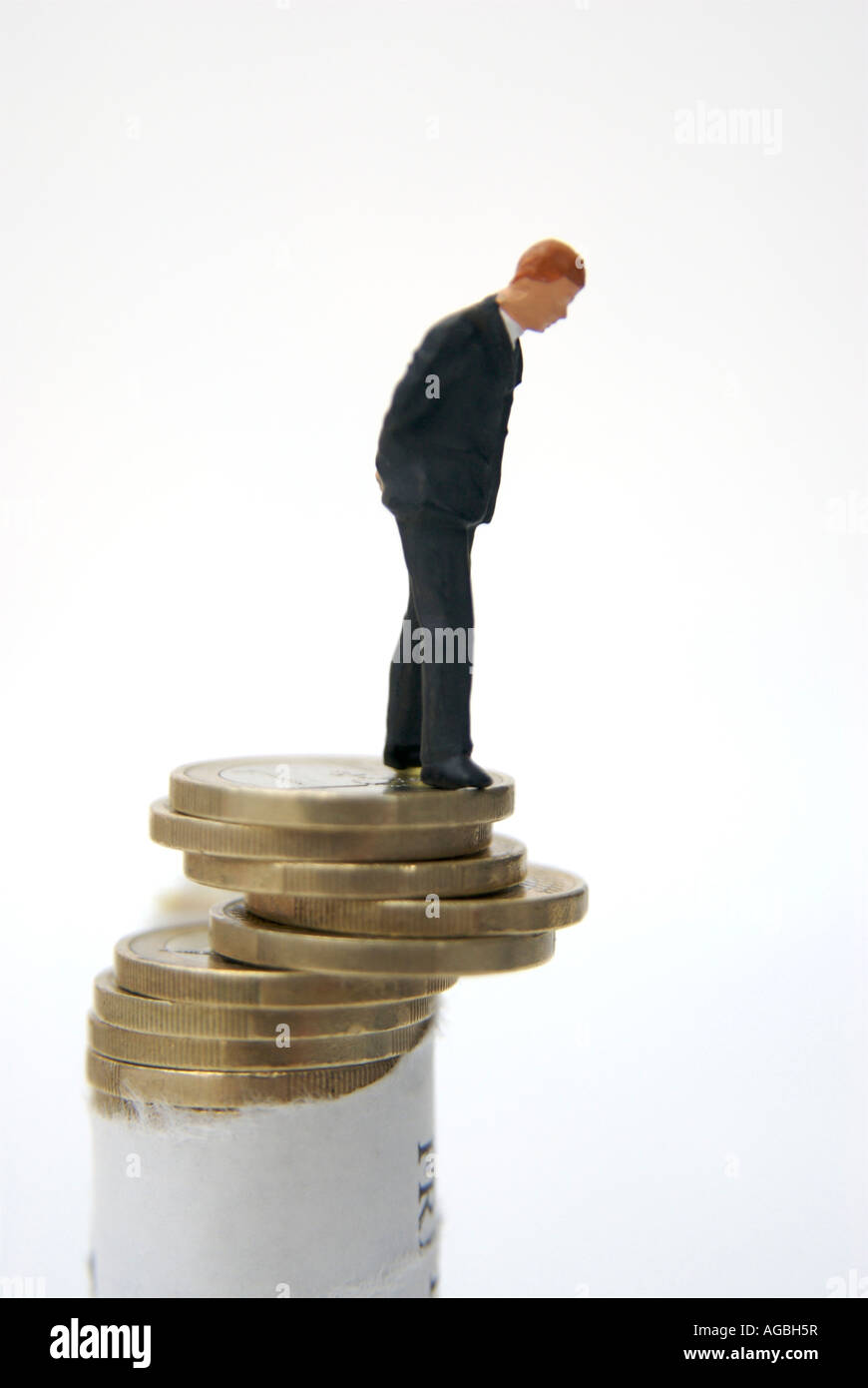 Businessman looking over the edge of a pile of euro coins - EU financial crisis / economic collapse / instability - Stock Image