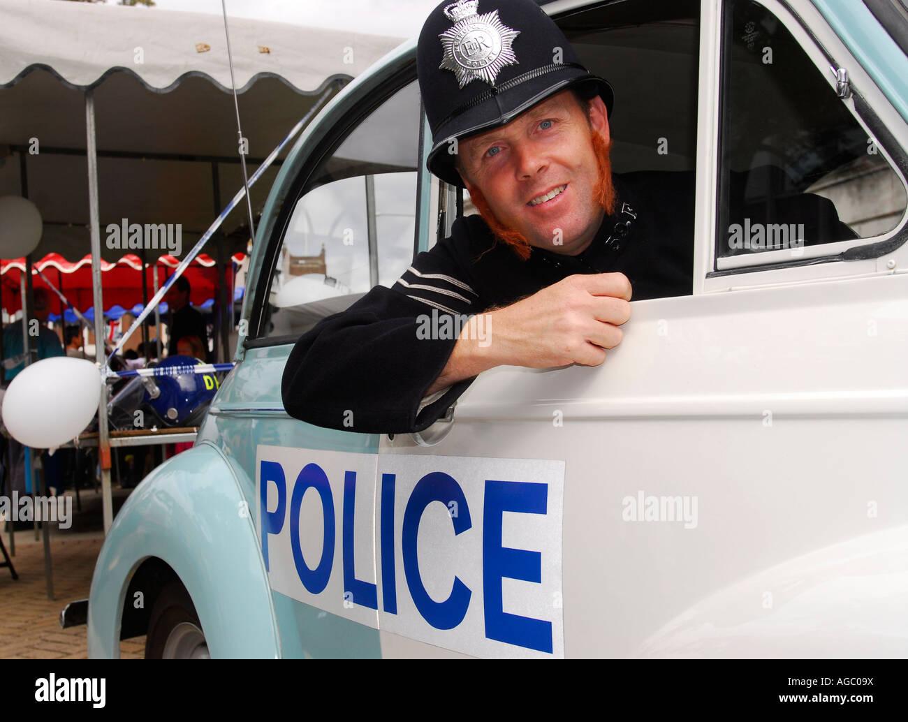 Police Officer in retrospective uniform and patrol car at Kingston Carnival 2007, Kingston, Surrey, UK. - Stock Image