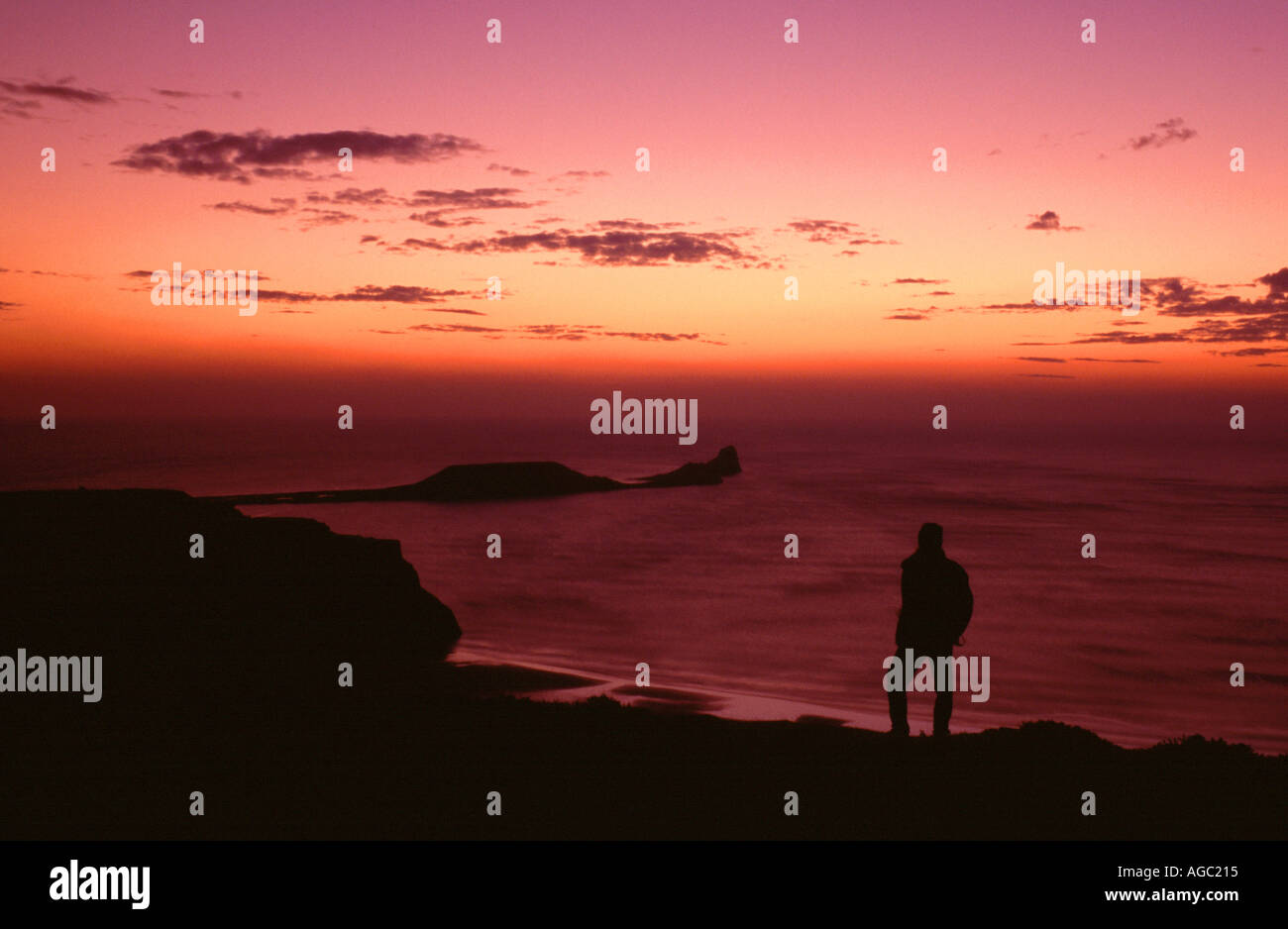 A FIGURE SILHOUETTED ON RHOSSILI DOWN WATCHING THE SUN SET OVER WORM'S HEAD, Gower Peninsula, West Glamorgan, South Stock Photo