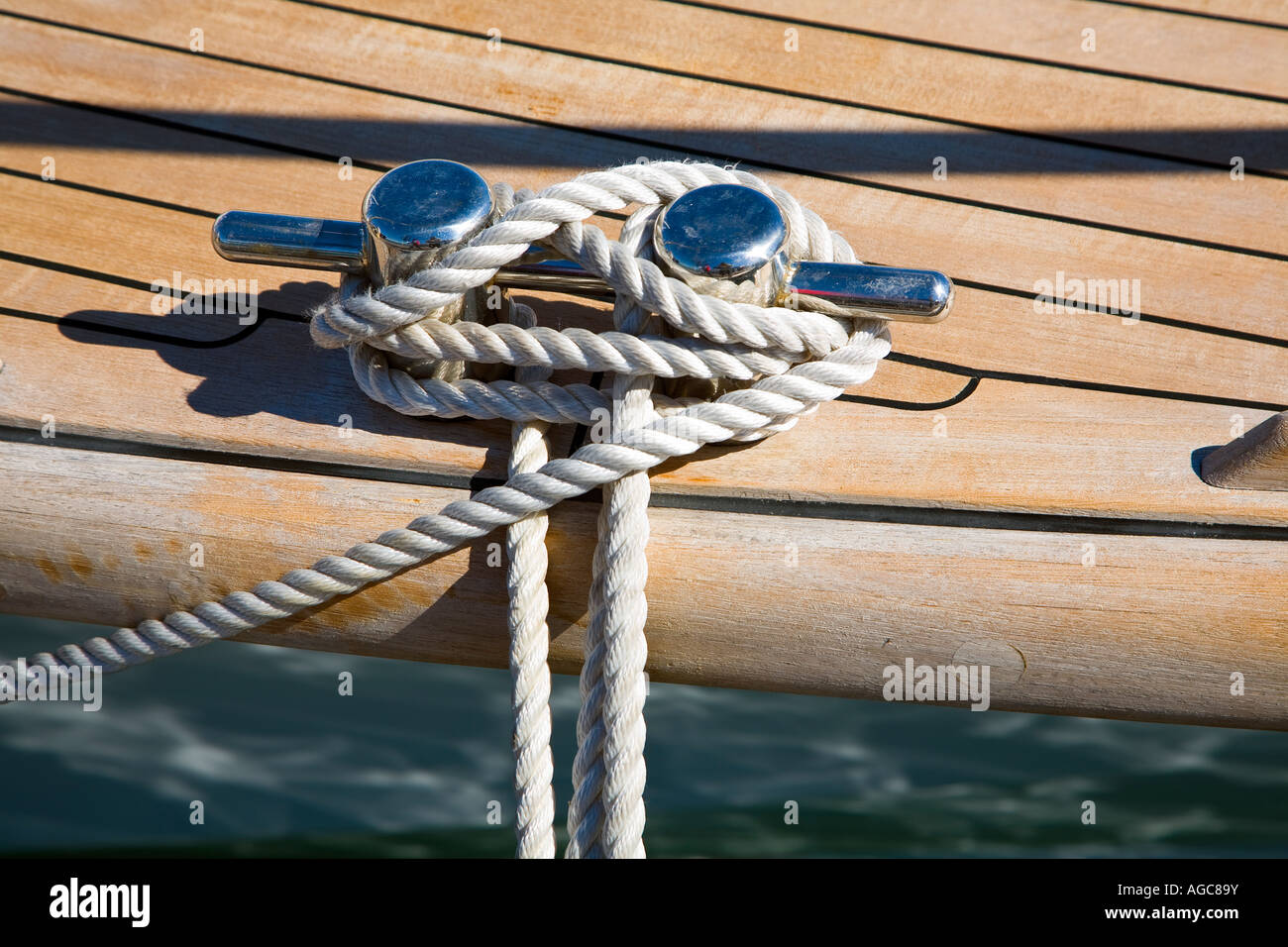 Rope around Polished Stainless Steel cleat on wooden deck - Stock Image