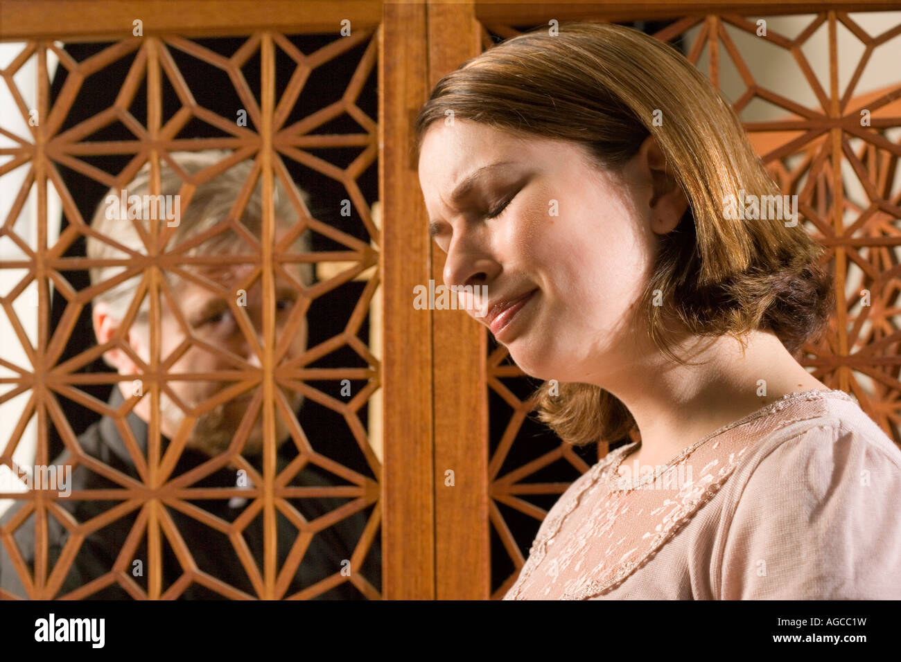 Woman talks to priest during confession. - Stock Image
