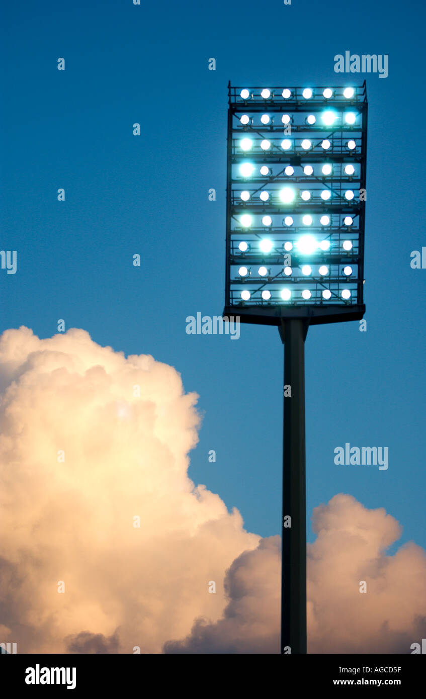 floodlight mast of a sports stadium against evening sky - Stock Image