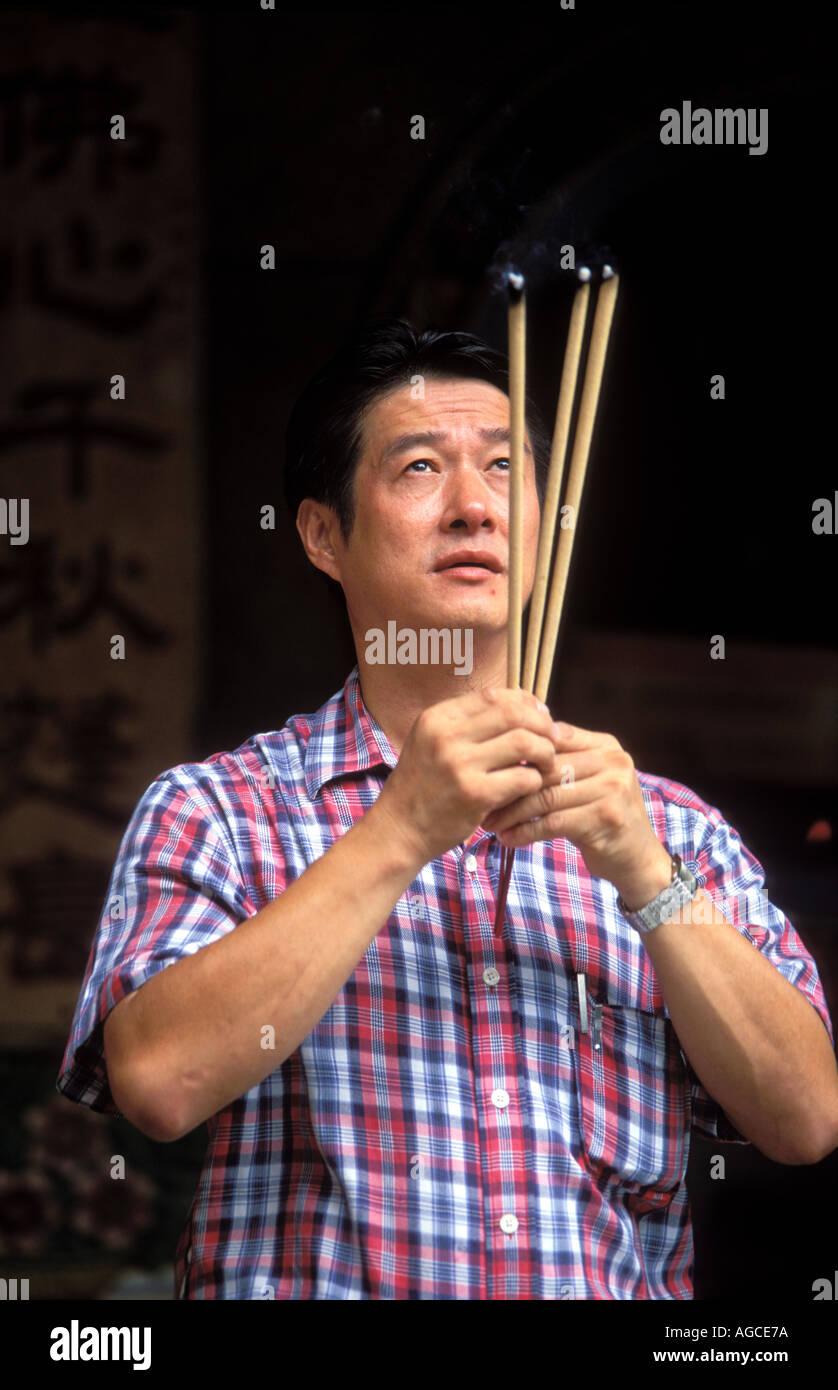 A Chinese man praying and holding burning incense sticks in