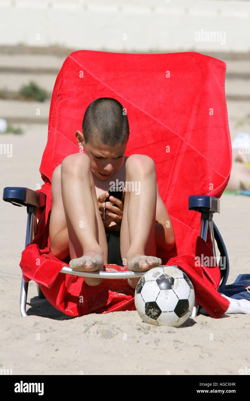 boy play mobile hendy telephone ball beach lounge - Stock Image
