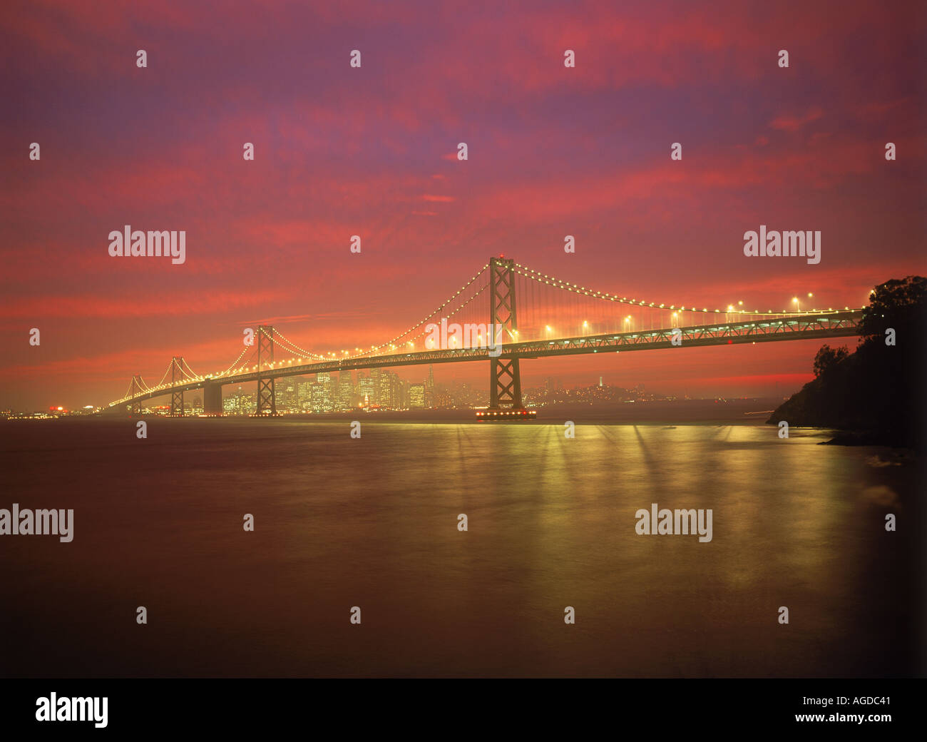 Oakland Bay Bridge under colorful sunset skies across San Francisco Bay - Stock Image