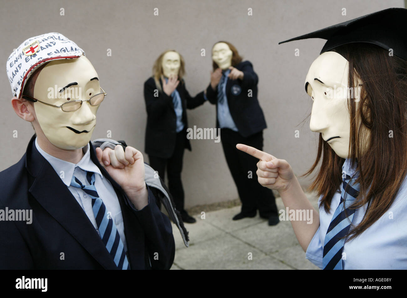 Drama students acting out a play using face masks - Stock Image