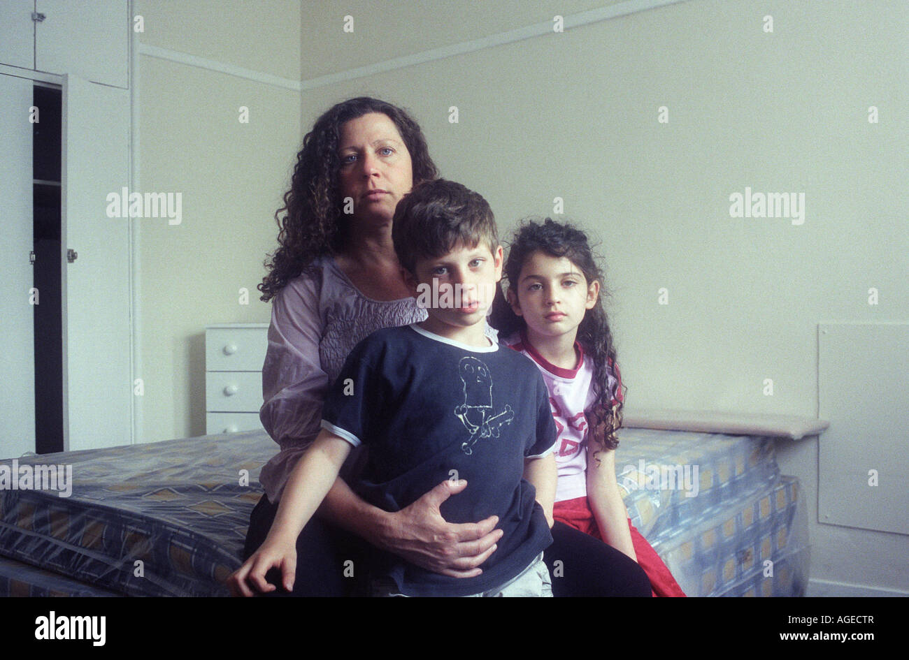 A pregnant single mother sits on a bed with her children in their new home, a flat in a council estate. Girl aged - Stock Image